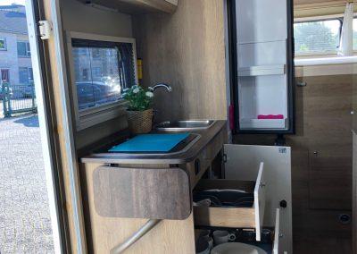 ruime keuken naast ingang met 3 pits fornuis, kasten en lades en zeer grote 142L automatische koelkast met flessenlade en vriesvak op gas,12v en 220v